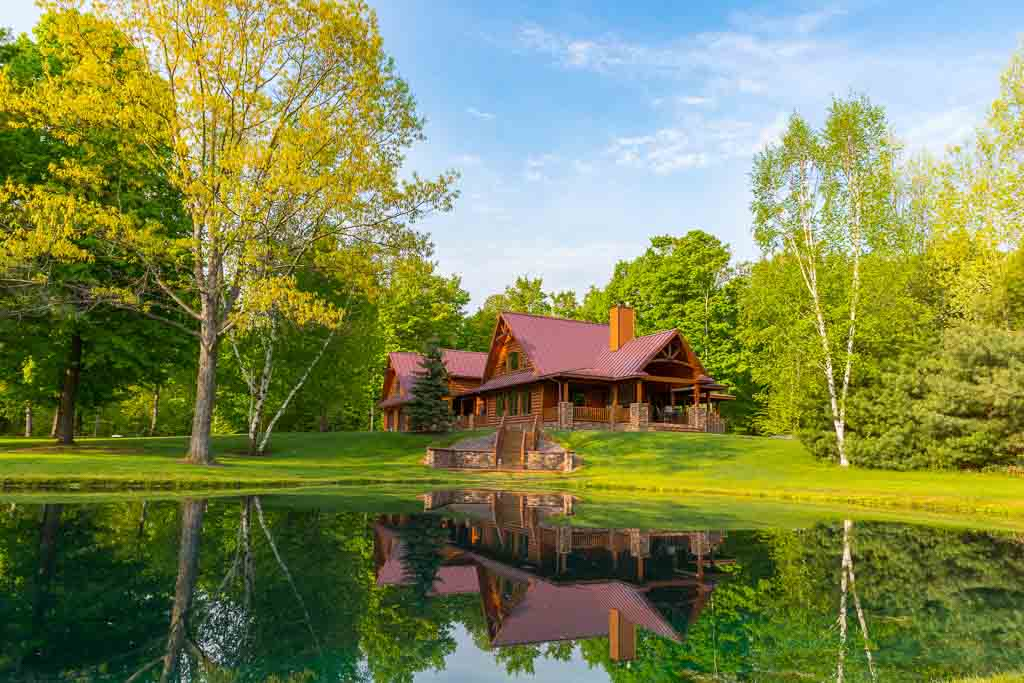 Log Siding: Home tucked into a wooded waterfront setting